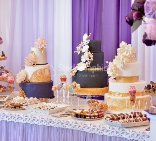 Candy bar with three big cakes. Cakes with black and white marzipan, beige flowers and golden lace.