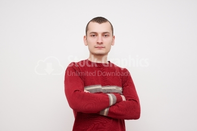 Casual young man looking at camera with arms crossed and