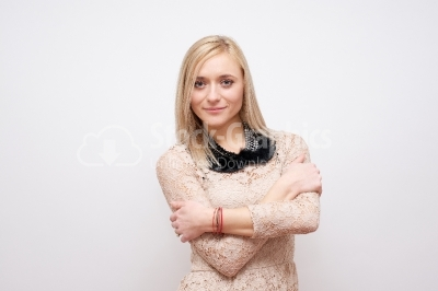 Casual young woman looking at camera with arms crossed and satis