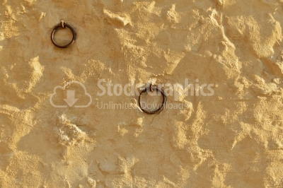 Cement wall with yellow plaster and two iron rings