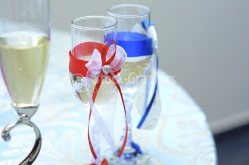 Champagne glasses with blue and red representing the bride and g
