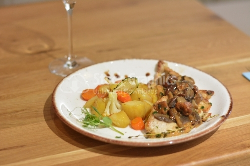 Chicken breast with sauteed mushrooms and vegetable garnish.