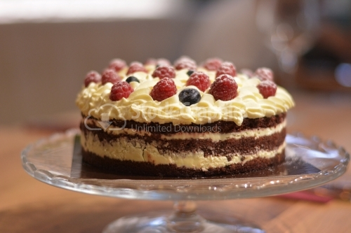 Chocolate vanilla cake, topped with white cheese frosting and raspberry pieces.