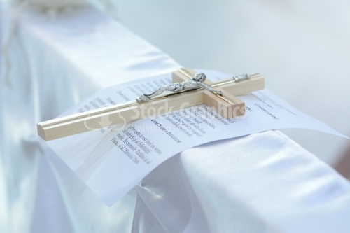 Christian cross and wedding vows on white satin
