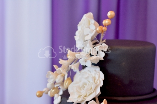 Close-up view wedding cake. Bouquet of beige flowers on cake with black marzipan