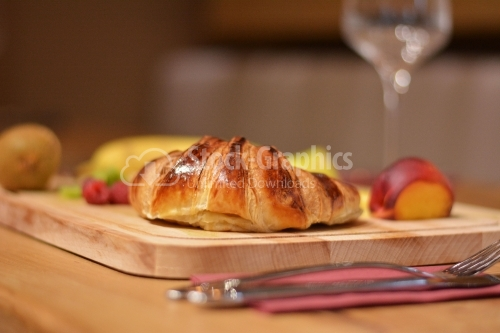 Croissant with various fruits around, placed on a wooden platter.