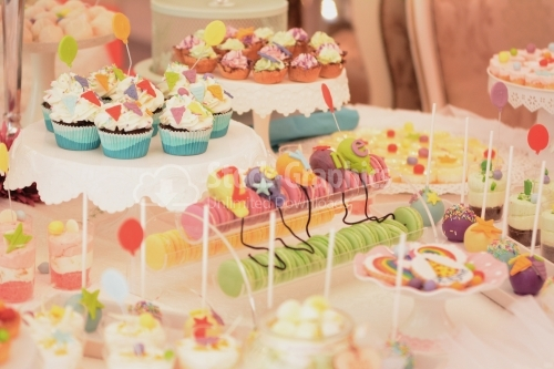 Cupcake and colorful macarons with variety marzipan decor. Candy bar