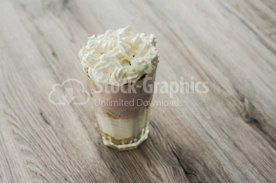 Dessert in glass with cream and fruit yoghurt on a wooden backgr