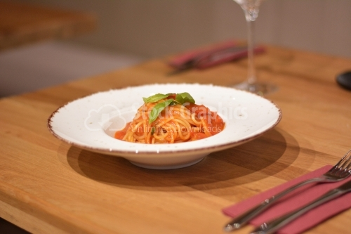 Detail of fresh pasta topped with tomato sauce and leaves of basil.