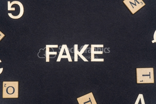 FAKE word written on dark paper background. FAKE text for your concepts