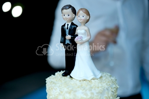 Figurines of the bride and groom on a milk wedding cake