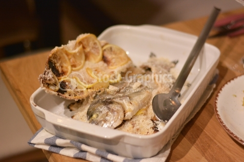 Fish in the salt crust in the oven placed in the white ceramic tray.