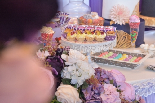 Flowers and various cakes on a table. Candy bar