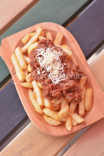 French fries with meat stew and grated cheese on top.