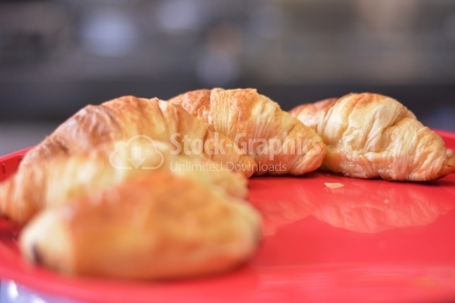 Fresh and tasty croissant over red background.