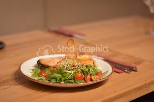 Fried fish with salad. The salad contains tomatoes, valerian, wheat germ and lettuce.