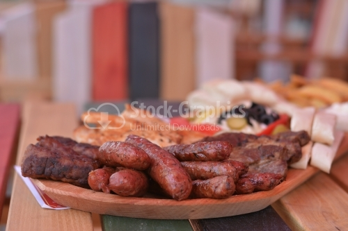 Fried sausages with herbs and grilled meat, all placed on a wooden tray.