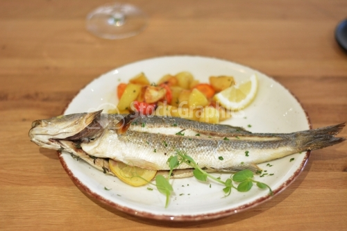 Fried trout fish with potato and pepper garnish.