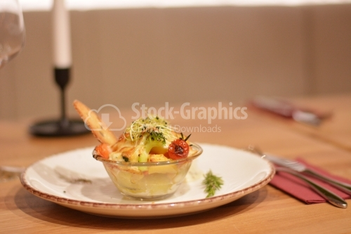 Glass bowl with au gratin potatoes, broccoli, tomatoes and wheat grains.