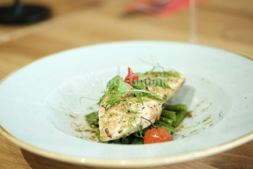 Grilled chicken breast, asparagus, tomatoes and dill on white plate.
