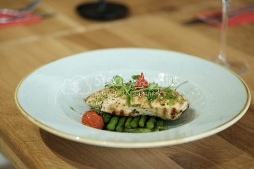 Grilled chicken breast on an asparagus bed on white plate.