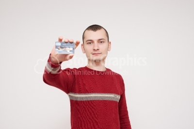 Happy smiling young man holding a credit card isolated on white