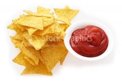 Healthy snack tortilla chips or corn chips, with tomato ketchup.