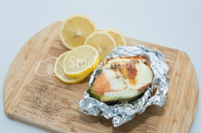 Hot snack with eggs and salmon, decorated with lemon