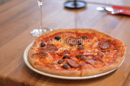 Italian pizza. Pizza with salami and olives.