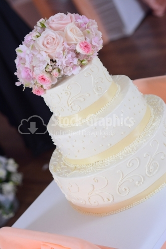 Ivory-colored wedding cake with a flower bouquet on top