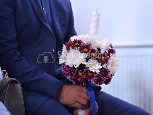 Man holding a candle with flowers for wedding