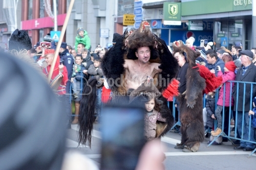 Man in natural bear's fur suit on the street. The annual festival of winter traditions and customs.