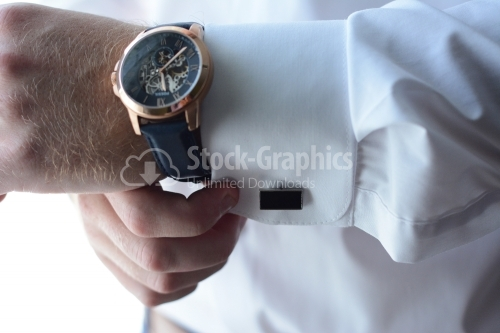 Man putting his watch and buttons on his shirt. Businessman. Groom.
