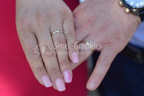 Married couple. Woman's and man's hand with wedding rings in sight.