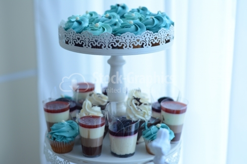 Muffin with blue cream and pudding in layers. Candy bar