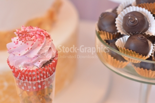 Muffin with strawberry cream and small red candies and chocolate sugar fondant