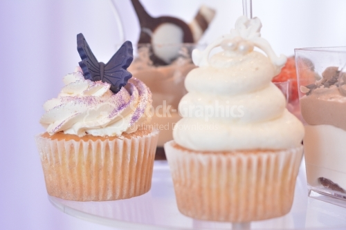 Muffin with whipped cream and glitter purple. Purple marzipan butterfly
