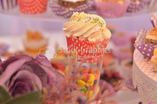 Muffin with whipped cream and rainbow candy. Candy bar