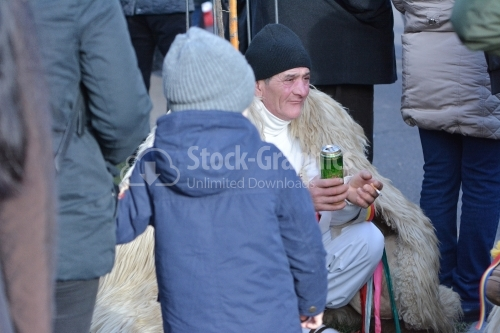 Old man dressed in a shepherd, drinking beer and smoking, at the winter festival. Authentic traditional from Romania