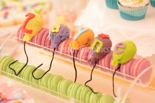 Pink and green macarons and colorful marzipan balloons