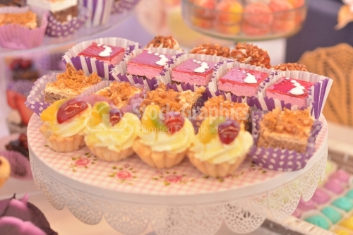Plate with assorted cakes: cream and strawberry jelly cakes, walnut and crunchy caramel cake and vanilla cream mini tarts
