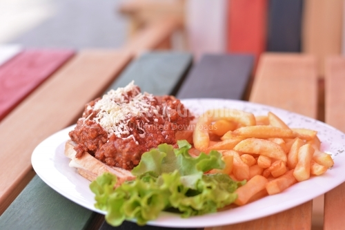 Plate with minced meat sauce on toast, french fries and salad.