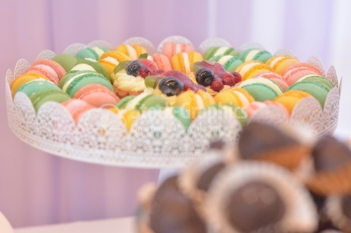 Platter with colorful macarons and mini tarts with fruit and vanilla cream in the middle