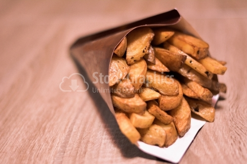 Potatoes wedges in paper cone on a wooden table