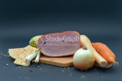 Prague ham on wooded cutboard with onion carot and cucumeber