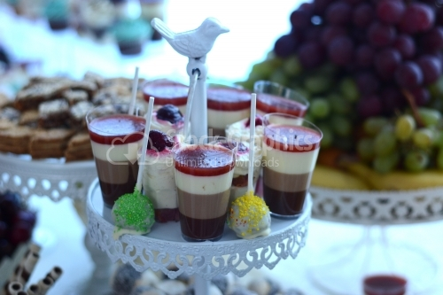 Pudding in layers with cocoa, strawberries, whipped cream, cappuccino and fruit combined with fondant on a stick