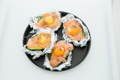 Raw eggs on pieces of salmon and avocada, put in the tray