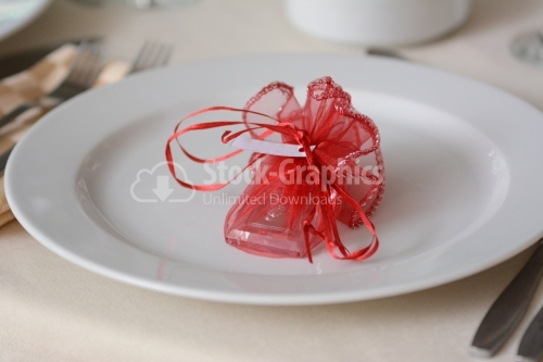 Red gift with bow on a white plate