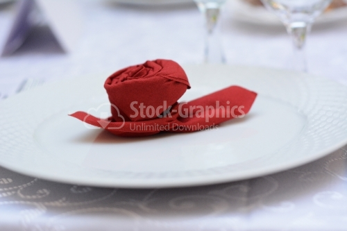 Red rose made of paper on a white plate