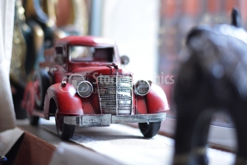 Red vintage toy car in a boutique.